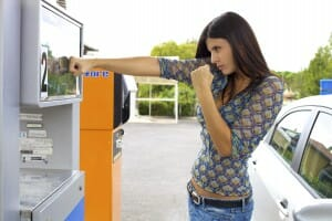 Beautiful brunette punching gas station because of high price