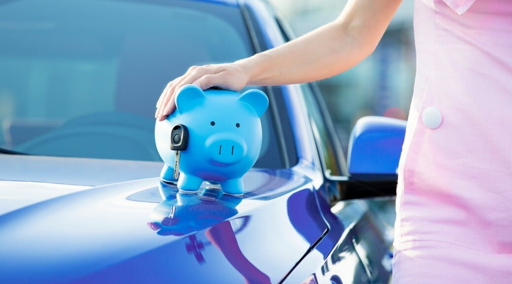Cropped image woman customer car, piggy bank, key on hood