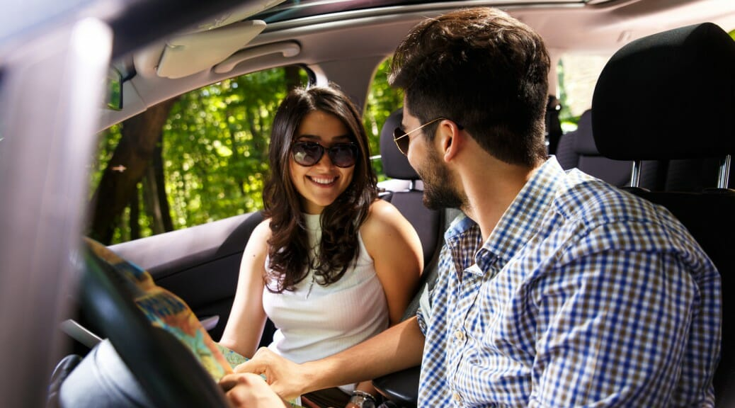 Happy young couple with a map in the car. They are using map on road trip.