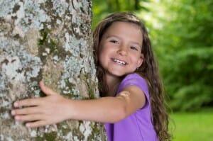 Kleines Mädchen umarmt Freudestrahlend einen Baum