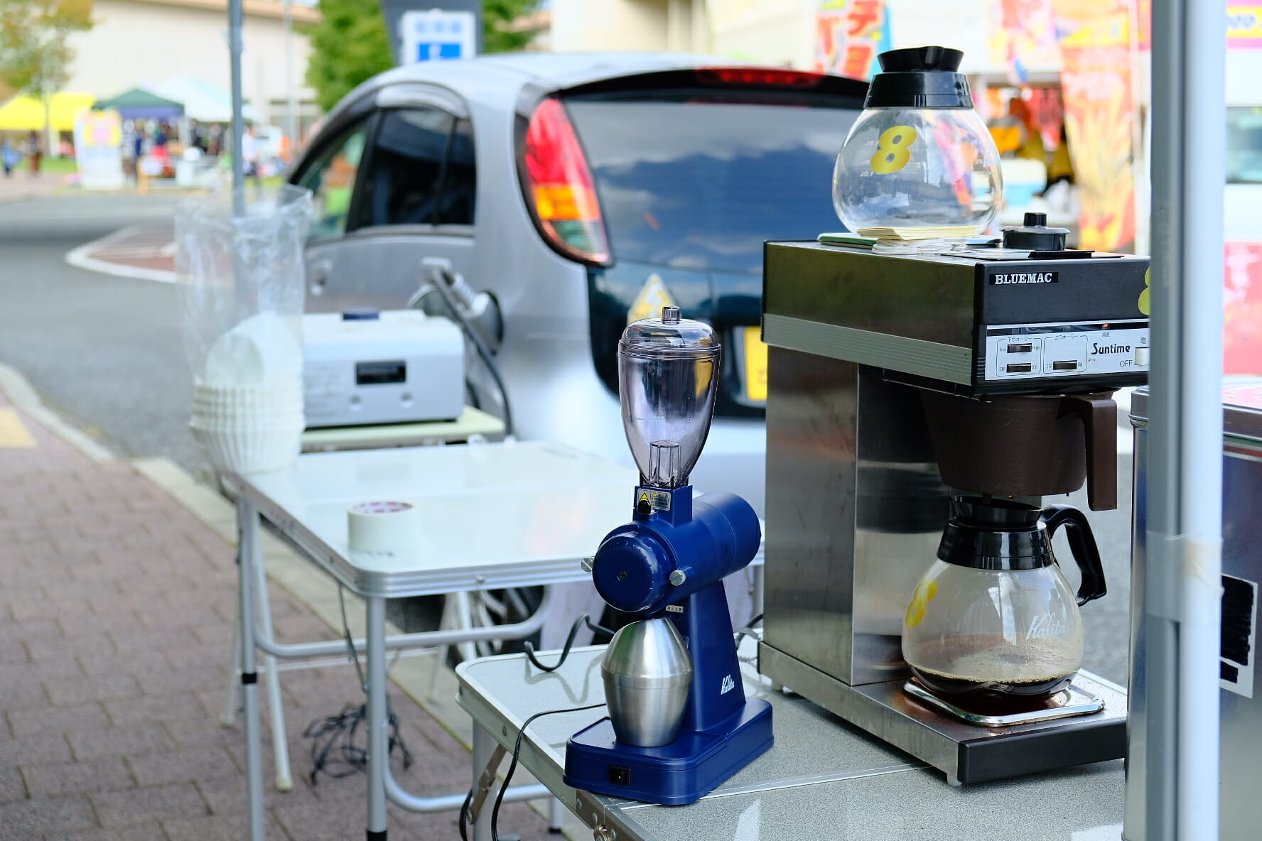 後方のi-MiEV Mタイプからの電力で、、手前のコーヒーミルと珈琲マシンを動かして珈琲を淹れているところ。1,500Wまで出せるので、電子レンジやホットプレートも充分動かせる。