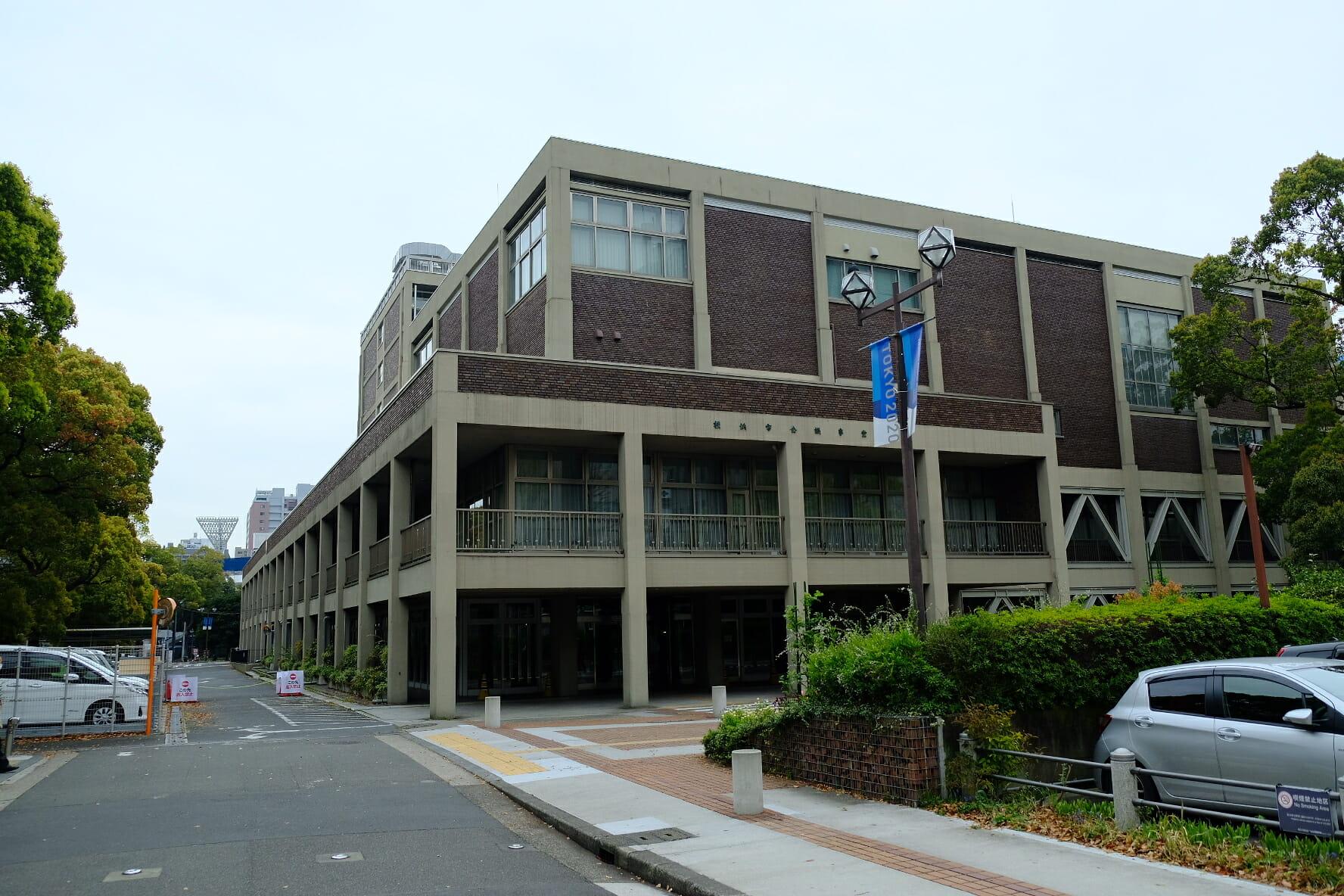 JR根岸線「関内駅」に隣接し、横浜スタジアムにも隣り合う横浜市の市庁舎。後ろに球場の照明塔が見える。
